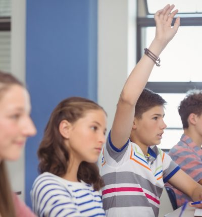 Student raising hand in classroom at school